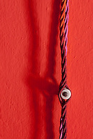 A close up of the vibrant vermilion walls of a bedroom painted by Marina Sinibaldi