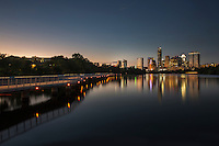Magical view of dusk setting on the Boardwalk Trail on Lady Bird Lake overlooking the downtown Austin Skyline - Stock Image.