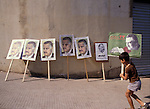 A boy carries a placard honoring Gamal Abdel Nasser across a line of Nasser signs prepared for a Beirut, Lebanon demonstration celebrating the death of Eqyptian President Anwar Sadat in 1981.