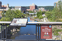 A sign provides information on the Saw Mill River Daylighting initiative in Van Der Donck Park in Yonkers, New York.