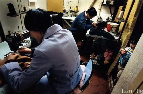 France, Paris, 05-2003..Illegal Chinese at a make-shift garment sweat-shop in Paris. They are a new wave of immigrants from China?s northeast, home to millions of former cradle-to-grave factory workers laid off by closures. ..When the work is done, the family sleep on the floor.