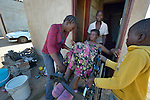 Delina Nleya gets help from her children as she leaves her house in Bulawayo, Zimbabwe. Nleya suffered a spinal cord injury and uses a wheelchair provided by the Jairos Jiri Association with support from CBM-US.