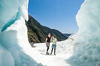 Two women enjoying spectacle of  beautifully coloured ice cave on Franz Josef Glacier,  Westland Tai Poutini National Park, West Coast, UNESCO World Heritage Area, South Westland, New Zealand, NZ