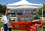 Old Westbury, New York, United States. 7th June 2015. JOHN GIORDANO of Whitestone, at left, and a fellow Marine veteran, hold a red Marine Corps League banner, in front of FREE HUGS By a MARINE fundraising booth of the Marine Corps League North Shore Queens Detachment #240 at the 50th Annual Spring Meet Car Show sponsored by Greater New York Region Antique Automobile Club of America. Over 1,000 antique, classic, and custom cars participated at the popular Long Island vintage car show held at historic Old Westbury Gardens.