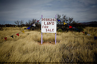 Land For Sale.  Arizona...Scenes from the US-Mexico Border between Douglas and Nogales, Arizona.  The high, arid landscape dividing these two frontier towns serves as a major portal for undocumented immigrants as well as a thoroughfare for human and drug trafficking.  The Bush administration approved 2.7 billion dollars for the construction of a fence along the 2000 mile border area.  The fence is not contiguous and, at many points, shows obvious signs that it serves only as a hurdle not as a roadblock.  The Obama administration has yet to decide whether it will complete construction of the fence which, even according to its mandate, will not bridge the entire border, rather covering urban and high-traffic areas.  .