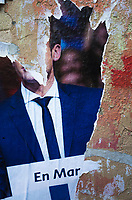 """France. Ile de France. Paris. Partially torn campaign poster of French presidential election candidate Emmanuel Macron for the centrist party """"En Marche"""". 21.04.17 © 2017 Didier Ruef"""
