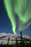Northern lights appear over Grayling Lake, in the foothills of the Brooks Range mountains, Arctic, Alaska