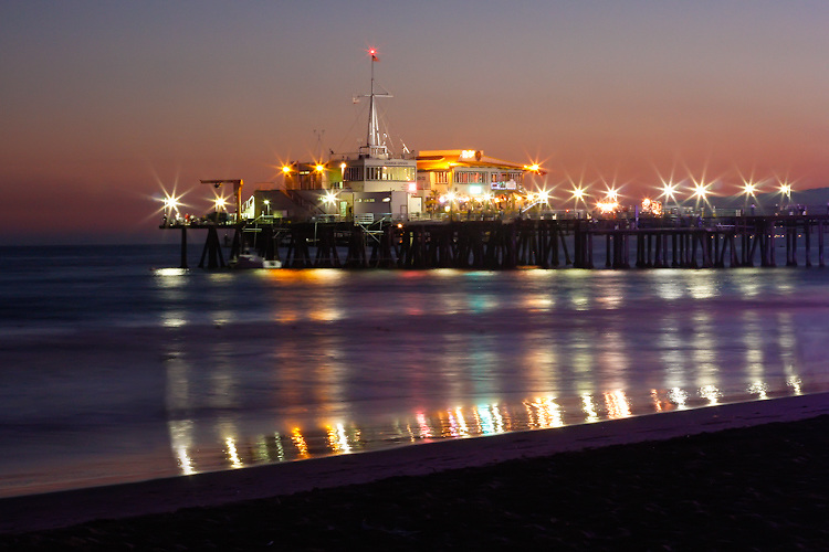 The end of the Santa Monica Pier lights up at night as it juts out over the water at dusk.
