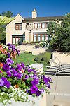 sunny summer image of colorful pink and purple summer annuals spilling out of an interesting raised planter box built in to a stucco wall that terraces down the back yard of a European-style estate house with blue summer sky above
