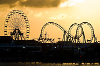 Early morning sunrise silhouettes the roller coaster and ferris wheen on the boardwalk at Ocean City, Maryland.