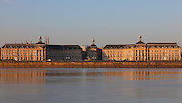 Place de la Bourse (Stock Exchange Square) or Place Royale, built 1730-55 by architect Ange-Jacques Gabriel during the reign of King Louis XV, seen from the Bastide district across the river Garonne, Bordeaux, Aquitaine, France. The royal square is a symmetrical rectangular space with the Stock Exchange to the North, Farms Hall to the East, a central building to the West and the Garonne River to the South. The buildings are reflected in the Miroir d'Eau, a 130x42m reflecting pool by Michel Corajoud and J M Llorca, inaugurated in 2006. The square forms part of the Port of the Moon and is listed as a UNESCO World Heritage Site, and the buildings are listed as historic monuments. Picture by Manuel Cohen