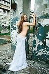 Girl with long hair and naked upper  body is looking over her shoulder next to decrepit walls