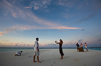 November 27th, 2008_MALDIVES_ People enjoy a cocktail party on a small sand island near  the Soneva Fushi resort island in the Baa Atoll, Maldives.  Soneva Fushi is a leader in green practices and plans to be carbon neutral by 2010 by implementing projects such as a deep-sea water cooling system to replace it's traditional air conditioners.  Photographer: Daniel J. Groshong/Tayo Photo Group