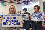 "Westbury, New York, USA. January 15, 2017.  L-R, AUDREY CIUFFO, HELENE MANAS, and FRANCINE GOLDSTEIN, members of Bellmore-Merrick Democratic Club, are holding protest signs at the ""Our First Stand"" Rally against Republicans repealing the Affordable Care Act, ACA. ""The Silent Majority Speaks"" posters say: ""IF YOU CARE - PROTECT HEALTHCARE!"" and: ""DON'T MAKE AMERICA SICK AGAIN.""  It was one of dozens of Bernie Sanders' nationwide rallies for health care that Sunday."