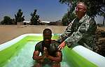 Marine Sgt. Brandon Wolfolk - Kilo Co. 3rd Battalion 8th Marines (3/8)  - is baptized by 1st Brigade 1st Armored Division Chaplain Major Michael Wood at 3/8's base in Ramadi, Iraq on Sat. Aug. 5, 2006.