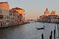 The Grand Canal, with the Basilica di Santa Maria della Salute, designed by Baldassare Longhena in Baroque style, built 1631-87, Venice, Italy. Many of the houses and palazzos fronting the canals are in Venetian Gothic style, a style originating in the 14th century and combining Gothic lancet arches with Byzantine and Moorish influences. The city of Venice is an archipelago of 117 small islands separated by canals and linked by bridges, in the Venetian Lagoon. The historical centre of Venice is listed as a UNESCO World Heritage Site. Picture by Manuel Cohen