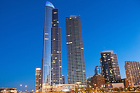 A dusk view of the residential towers of Museum Place in Chicago which blends energetic architectural forms with postmodern materials to create a design which elevates Chicago's world-class architectural reputation. Floor-to-ceiling windows, lively diagonal expressions and exposed steel elements are the hallmarks of Museum Park Place and combine to create a building whose composition is unlike any other on Chicago's lakefront.
