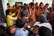 A health volunteer takes the MUAC reading while caretakers and family workers gather to have their children checked during a mass screening at the local health centre in Inarwa in Saptari, Nepal.