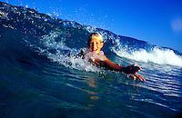 Boy body surfing in wave on the Big Island