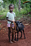 Loudjina Jean, a 7-year old girl in Chalo, Haiti, holds one of two female goats her family received from a church-sponsored aid agency, as part of its work to combat hunger and increase food production in the Haitian countryside. The family, which has eight children and had no goats before receiving the new pair, will eventually pass on goats to another family when its animals have offspring.