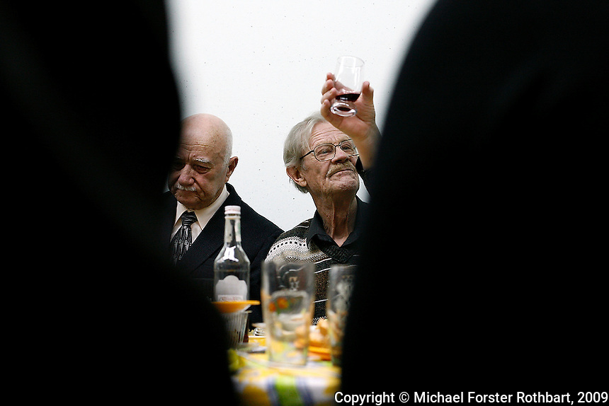 World War II veterans and other Chernobyl plant retirees gather in Slavutych, Ukraine, to observe Red Army Day, a holiday originally dedicated to veterans of the Russian and Soviet Armed Forces.  <br /> ------------------- <br /> This photograph is part of Michael Forster Rothbart's After Chernobyl documentary photography project.<br /> &copy; Michael Forster Rothbart 2007-2010.<br /> www.afterchernobyl.com<br /> www.mfrphoto.com <br /> 607-267-4893 o 607-432-5984<br /> 5 Draper St, Oneonta, NY 13820<br /> 86 Three Mile Pond Rd, Vassalboro, ME 04989<br /> info@mfrphoto.com<br /> Photo by: Michael Forster Rothbart<br /> Date:  2/2009    File#:  Canon 5D digital camera frame 60662<br /> ------------------- <br /> Original caption: .In Slavutych, Ukraine, members of the Nezdaiomtsya pensioners' group gather to observe Red Army Day, a holiday originally dedicated to veterans of the Russian and Soviet Armed Forces. Today, the holiday is officially called Defender of the Fatherland Day, but colloquially it is simply called Men's Day (???? ??????)...Most members of Nezdaiomtsya are Chernobyl retirees. Both men pictured here are World War II veterans. Slavutych is the new city built after the Chernobyl accident to replace the abandoned city of Pripyat. After the April 26, 1986 accident at the Chernobyl Nuclear Power Plant, the population within 30 kilometers was permanently evacuated, including residents of Pripyat and many villages. .-------------------.