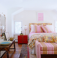 In the guest bedroom the lamp on an antique red-lacquered bedside chest is a 1940's Josef Frank design and the bed is covered with linens in contrasting florals and stripes