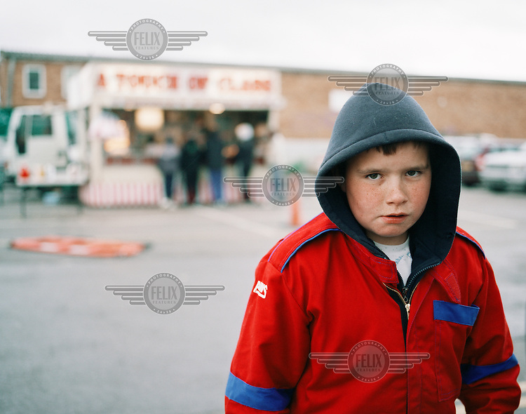 """A boy dressed in overalls makes his way into Wimbledon Stadium to watch the first banger race of the day after having chips from the fast food stall """"A Touch of Class"""" at Wimbledon Stadium in London. Banger racing is practiced by small communities throughout the country. They invest all their time and money in doing up old cars, only to smash them to pieces by the end of the week. They've been doing it for generations. Whether as a driver or spectator, the ritual satisfies a common human urge: to create and to destroy..."""