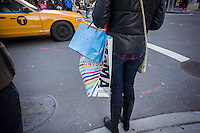 A shopper in Soho  in New York with her shopping bags from the Museum of Modern Art and Marie Belle, Saturday, December 7, 2013. (© Richard B. Levine)