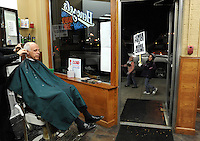 Lane Epstein gets his haircut at Henczel's Barber Shop as protesters of the recent layoffs of six Naperville police officers march from V.F.W post 3873 to the city's municipal center before the start of a weekly city council meeting in Naperville on Tuesday, November 16, 2010.  |  Jonathan Miano~Staff photographer