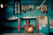A Cuban woman stands behind the shop counter, holding a flower, in front of a wall covered by photos of the revolutionary leaders, Santiago de Cuba, Cuba, 31 July 2008. During the Cuban Revolution, an armed rebellion at the end of the 1950s in Cuba, most of the revolutionary leaders started as no-name soldiers fighting in the jungle. Although the revolutionary leaders, after taking over the power, became autocratic rulers holding almost absolute power and putting the opposition in jail, for some reason Cuban people have never stopped to worship Fidel Castro, Che Guevara, Raul Castro and others. Cubans hang their photos and portraits on the wall in homes, shops and working places even they don't have to. The people of Cuba love their heroes.