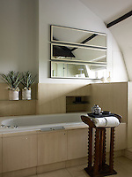 In the guest bathroom the floors, partition and bath surround are all constructed of the same pale stone