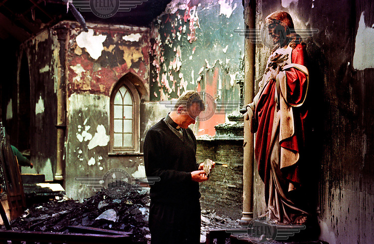 © David Rose / Panos Pictures..Father David Delargy,  a priest at St James church, Crumlin, holds a broken hand from a statue of Christ in the 200 year old chapel, after a night in which twenty Catholic churches were attacked. 3 July 1998. County Antrim, Northern Ireland.