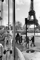 France. Ile-de-france Department. Paris. View on the Eiffel tower. A group of young schoolchildren and their teacher walk by sculpted horse on a carousel. 3.11.09 © 2009 Didier Ruef