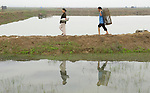 Nguyen Xuan Hien, who lost a leg to a landmine, walks home with his wife, Le Van Thoan, after harvesting shrimp from their pond in Bo Trach, Vietnam.
