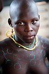 The head of an adolescent girl undergoing Dipo is shaved to identify her as a 'Dipo-Yo'. Her skin is decorated with scented dyes.