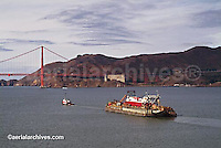 aerial photograph tug boat pulling loaded barge toward Golden Gate bridge California