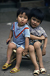 Two brothers share a chair in Hanoi, North Vietnam.  (Jim Bryant Photo).....