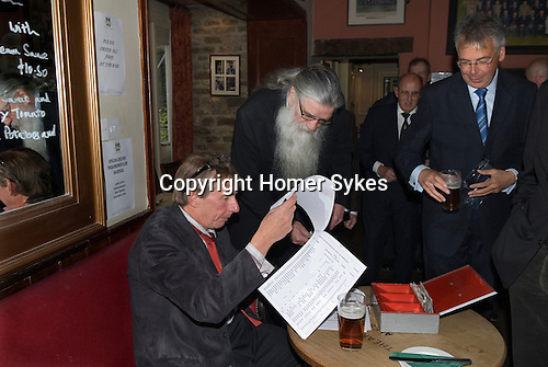 Askrigg Equitable Benevolent and Friendly Society. Askrigg north Yorkshire UK. Paying the annual subscription. Members in the bar of the Kings Arms Hotel before the annual walk to church behind the Friendly Society banner. Honorary members wear a white rosette, while ordinary members wear a blue one.