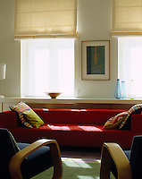 A long low sofa in this sitting room runs the length of the wall in front of a deep shelf that unites the two windows