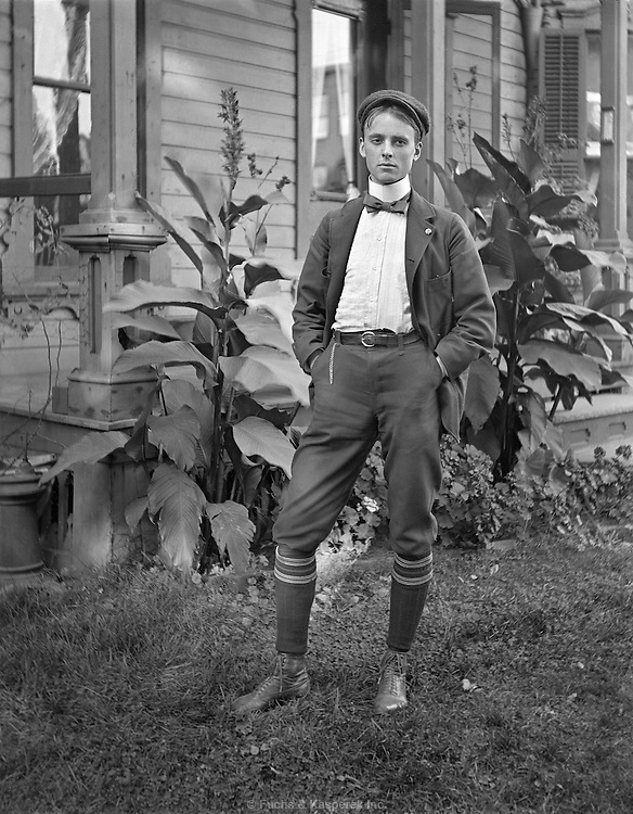 "A young man poses outside a home. Caption information reads ""Frank, home on furlough."" Circa 1900."