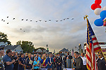 Freeport, New York, USA. September 10, 2014. A flock of birds flies overhead as pastor speaks at a dockside remembrance ceremony in honor of victims of the terrorist attacks of September 11 2001, at the boat Miss Freeport V, on Freeport's Nautical Mile. Further ceremonies were held on board the vessel, which sailed from the Woodcleft Canal on the South Shore of Long Island, on the eve of the 13th Anniversary of the 9/11 attacks.