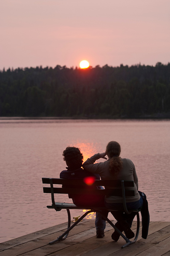 Visitors to Isle Royale National Park watch the sunset over Tobin Harbor.