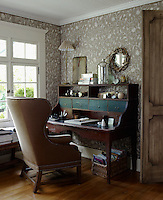 An antique French writing table is paired with a wing-backed armchair in a corner of the study