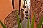 A woman walks down a cobble stone path in Bellagio, Italy a town on Lake Como