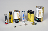 12-V lead-acid battery with selection of smaller batteries, white background.....