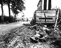 Men of the 8th Infantry Regiment attempt to move forward and are pinned down by German small arms from within the Belgian town of Libin.  Men seek cover behind hedges and signs to return the fire.  September 7, 1944.  Gedicks.  (Army)<br /> NARA FILE #:  111-SC-193835<br /> WAR &amp; CONFLICT BOOK #:  1061