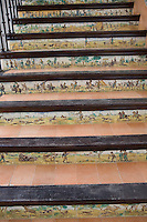 A staircase with tiles depicting images of rural hunting scenes