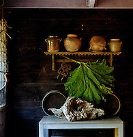 A dried leaf and gnarled wooden root sit beneath a collection of  earthenware pots on display on an old pine shelf