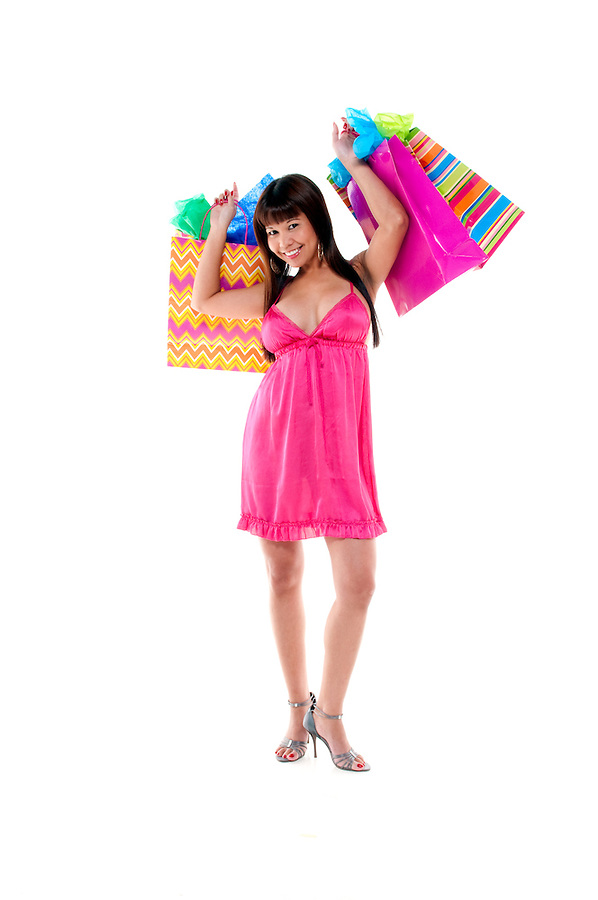 Young and sensual Asian girl with shopping bags and presents.