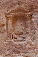 Sacred stone or baetyl at Sabinos Alexandros Station in the Siq, 2nd - 3rd century AD, Petra, Ma'an, Jordan. This votive niche in the Siq wall was carved by Sabinos Alexandros, master of religious ceremonies at Dara'a in Syria, and offers protection to those walking the Siq. It depicts the god Atagatis in human form on a throne with 2 lions. Below is a Greek inscription. Petra was the capital and royal city of the Nabateans, Arabic desert nomads. Picture by Manuel Cohen